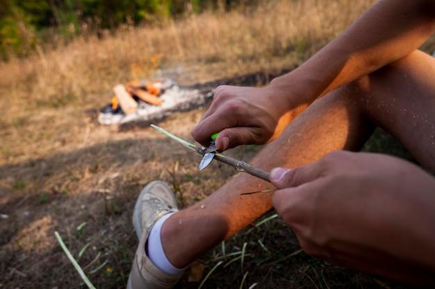 人は屋外で木の棒を彫る