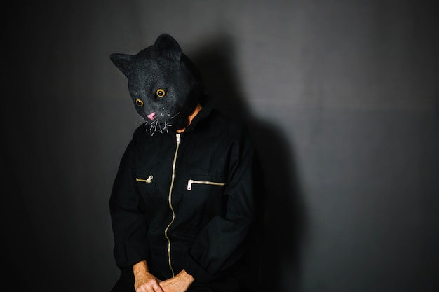 Person in cat mask in dark room