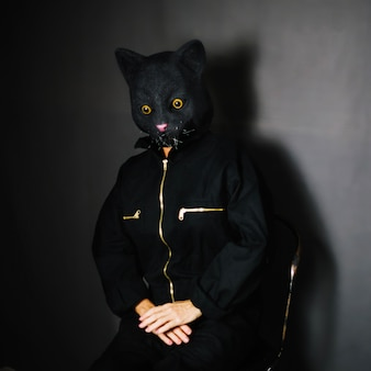 Person in cat mask sitting