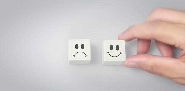 Person choose happy face block over sad face block