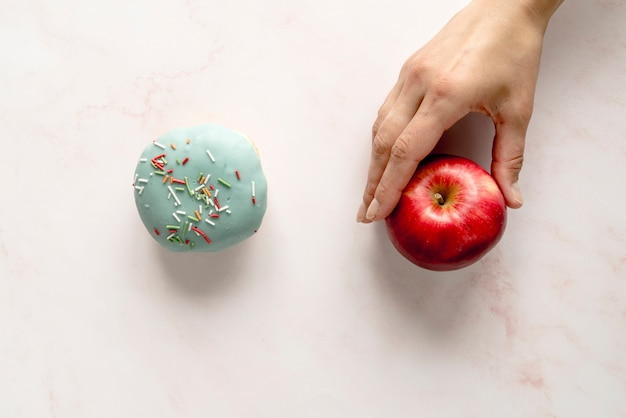 Person choosing apple over donut against white background