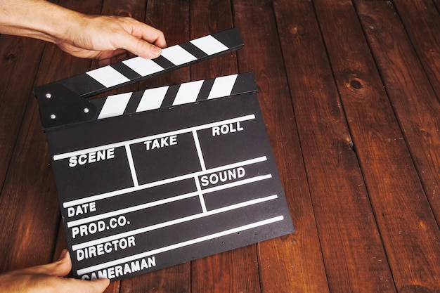 Person clapping clapperboard over wooden tabletop