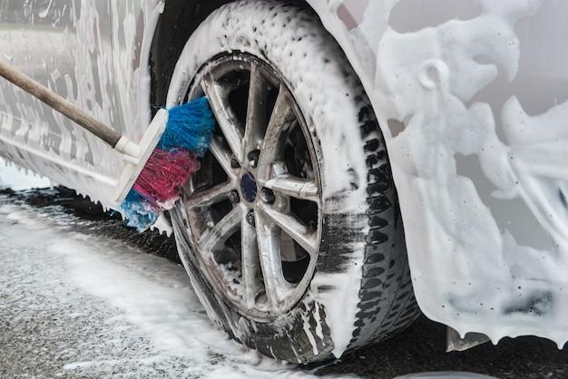 ブラシと泡で車のホイールを掃除する人