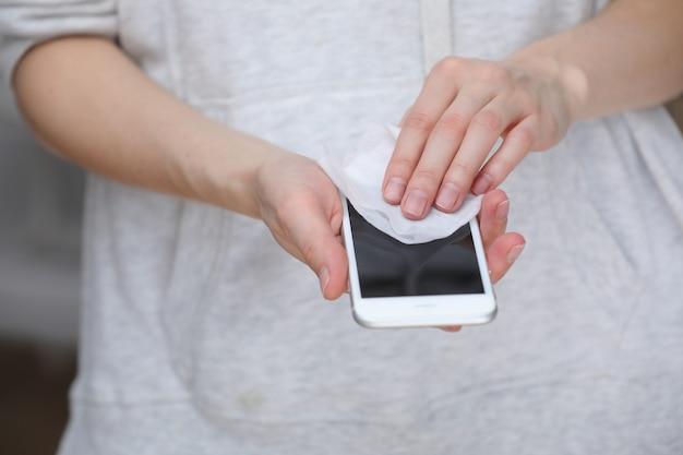 Экран мобильного телефона person cleaning с дезинфицирующими салфетками для чистого смартфона.