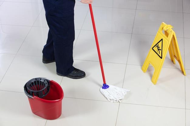 黄色い注意濡れた床の看板の近くの赤いモップで床を掃除している人