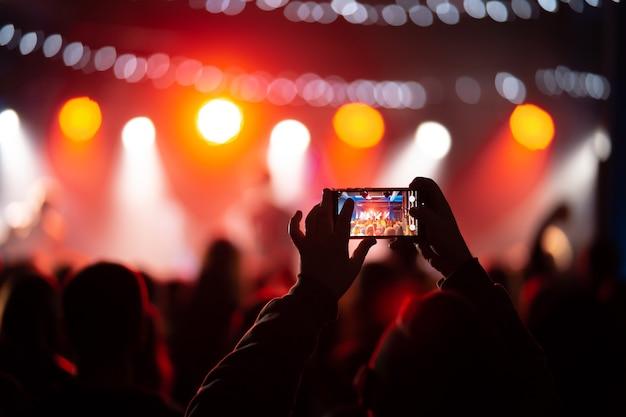 사람이 콘서트 도중 스마트 폰으로 비디오 녹화의 클로즈업