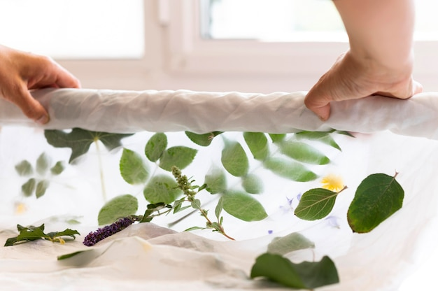 Person coloring a cloth with leaves