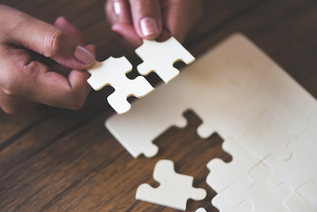 Person connecting jigsaw pieces