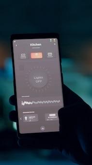 スマートフォンでスマートホームアプリのタッチ画面を使って家の明かりをつける人