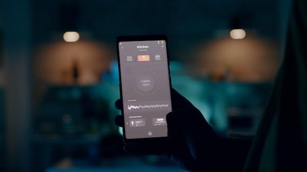 スマートホームアプリケーションのタッチスクリーンを使用して家の照明を制御し、モバイルでオンにする人...