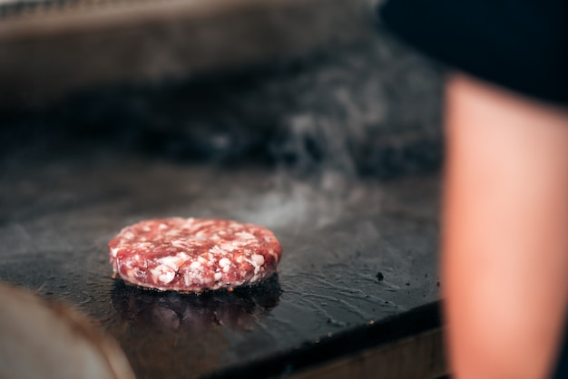 Person cooking burger patty.