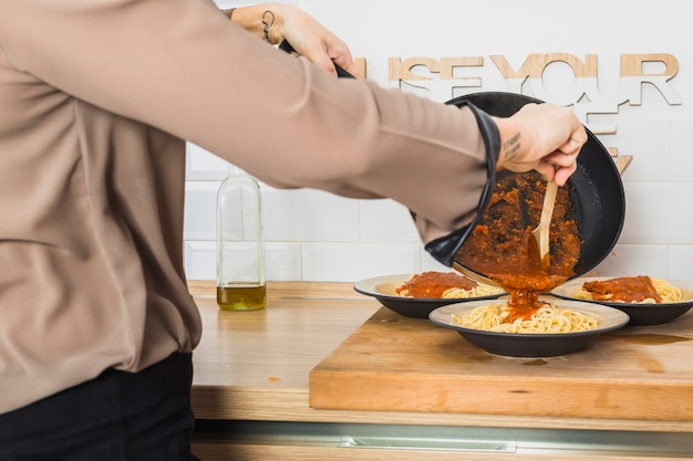 Person cooking pasta sauce in kitchen