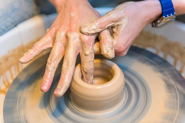 Человек, создающий глиняную чашку