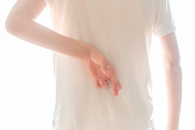 Person crosses his fingers behind his back and lying concept