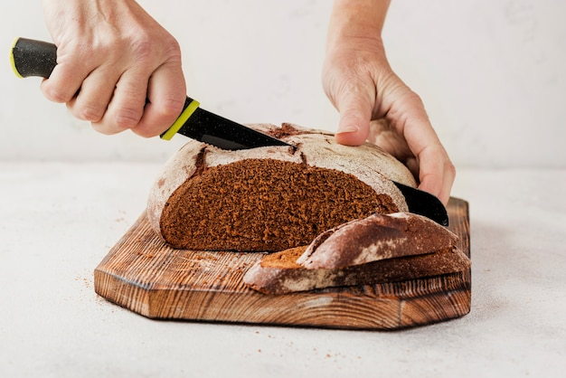 Person cutting bread on wooden board