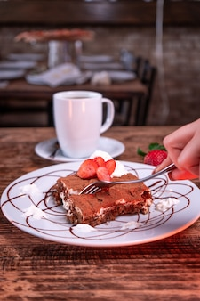 Person cutting a chocolate biscuit with strawberry next to a cup of coffee