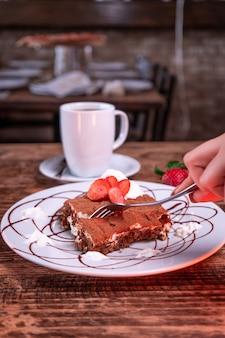 Persona che taglia un biscotto al cioccolato con fragole accanto a una tazza di caffè
