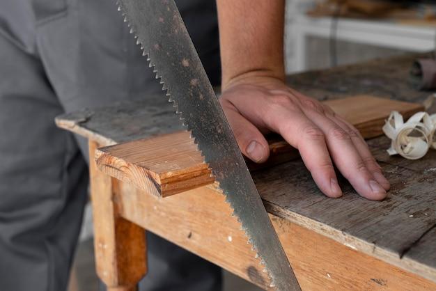 Persona che taglia il primo piano del legno