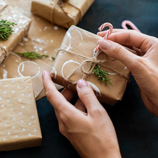 Человек, украшающий рождественский подарок конфетой