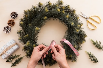 Person decorating Christmas wreath with ribbon