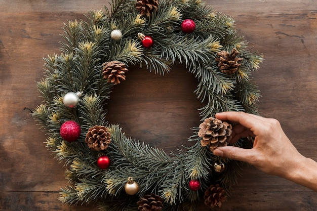 Person decorating christmas wreath