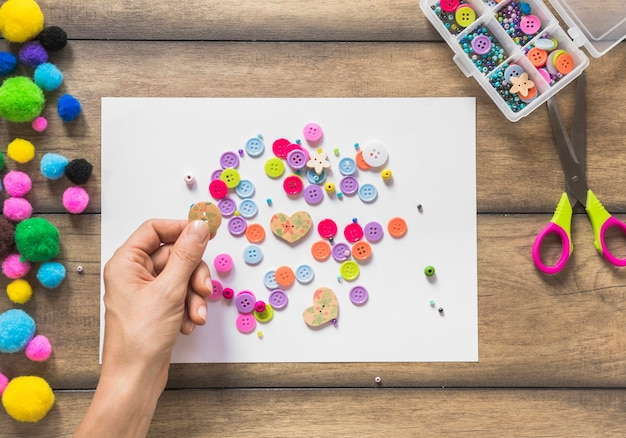 A person decorating white paper with colorful buttons over wooden table