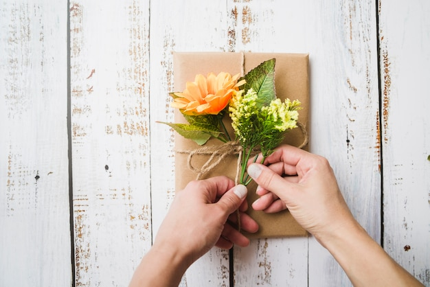 A person decorating the wrapped gift box with fake flowers on wooden background