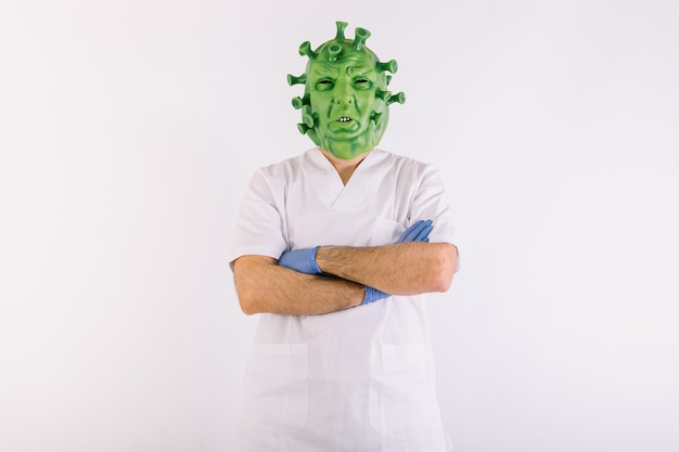 ラテックスマスクcovid19ウイルスでコロナウイルスに変装し、白い背景に腕を組んで医師のスーツを着ている人。