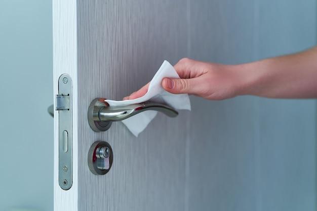 Человек дезинфицирует и очищает дверную ручку антибактериальными влажными салфетками для защиты от вспышки коронавируса