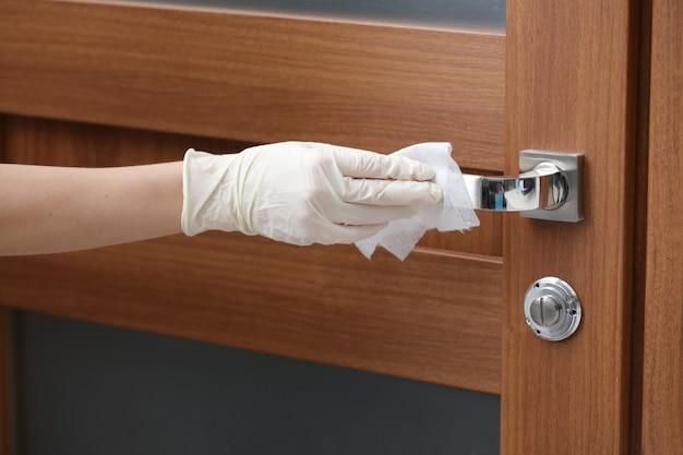Человек дезинфицирует и очищает дверную ручку антибактериальными влажными салфетками для защиты от вирусов, микробов и бактерий во время вспышки коронавируса и эпидемии гриппа. чистый дом