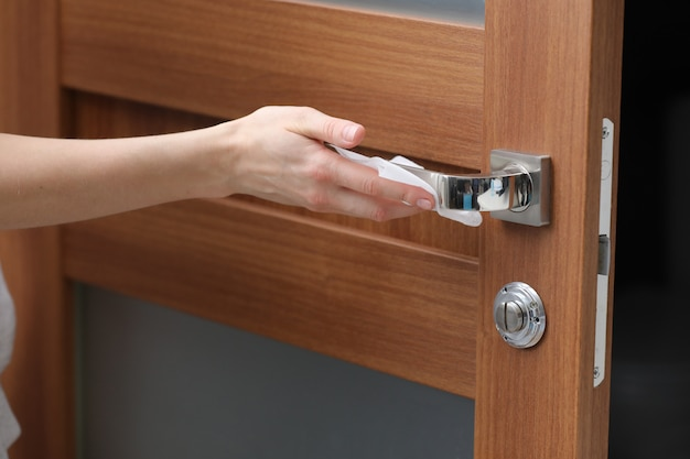 Person disinfects and cleans door handle with antibacterial wet wipes to protect against viruses, germs and bacteria
