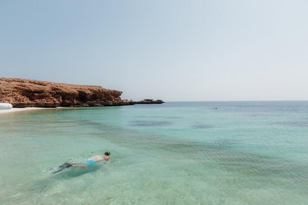 澄んだ青い空の下、岩の崖の近くの海でダイビングする人