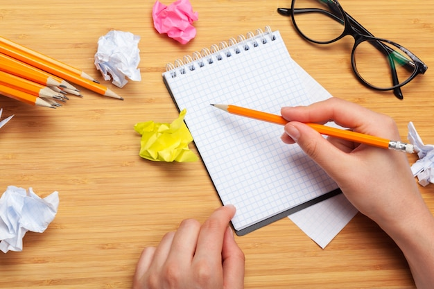 Person drawing in a notepad and office supplies on the table