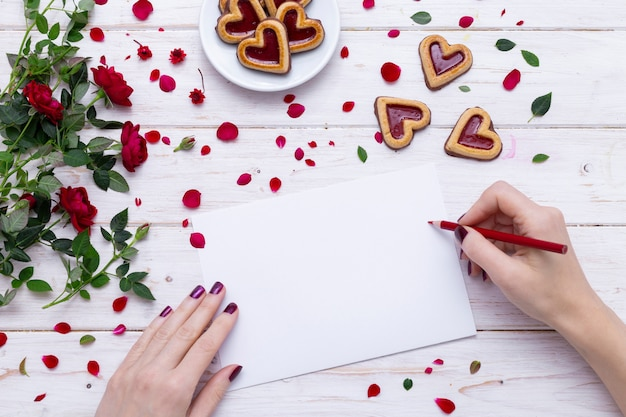 Person drawing on a white paper with a red pencil near heart-shaped cookies with rose petals