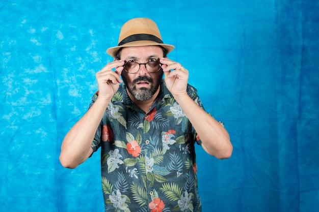 Человек, одетый как турист, в рубашке с принтом и удивленным лицом, снимает очки