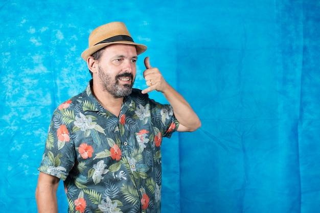 Человек, одетый как турист, в рубашке с принтом и с рукой на лице, как если бы он разговаривал по телефону