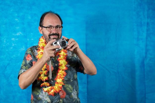 Человек, одетый как турист, с печатной рубашкой и фотоаппаратом в руке на синем фоне
