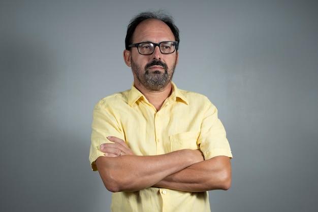 Человек, одетый в желтую рубашку со скрещенными руками на нейтральном фоне