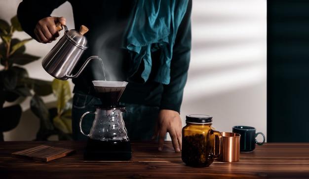 아침에 집에서 커피를 떨어지는 사람. 주전자에서 드리퍼에 뜨거운 물 붓기