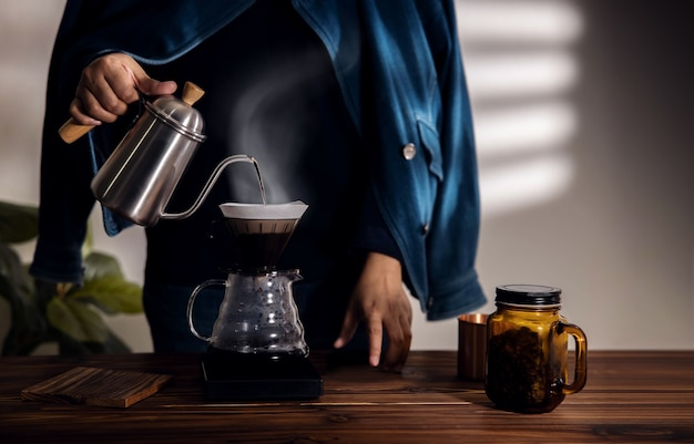 아침에 집에서 커피를 떨어지는 사람.