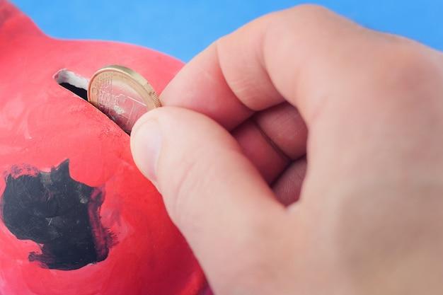 A person drops a coin of 1 euro into a piggy bank.