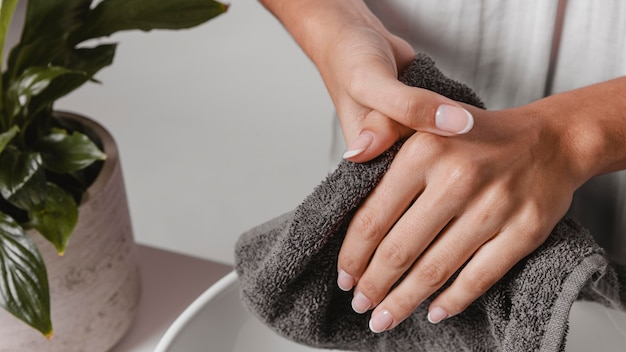 Person drying her hands on a towel close-up