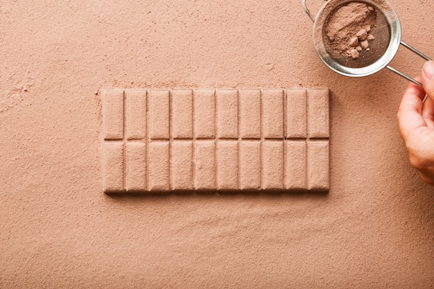 A person dusting cocoa powder from sieve on chocolate bar