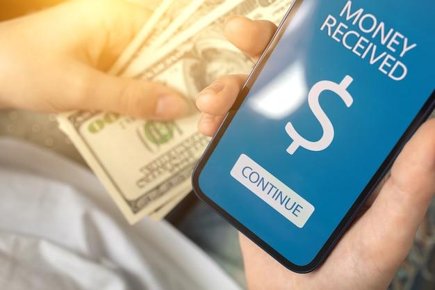 Человек, заработавший деньги с помощью мобильного телефона, концепция работы фрилансера из дома, экран полученных денег и доллар в руках, фото