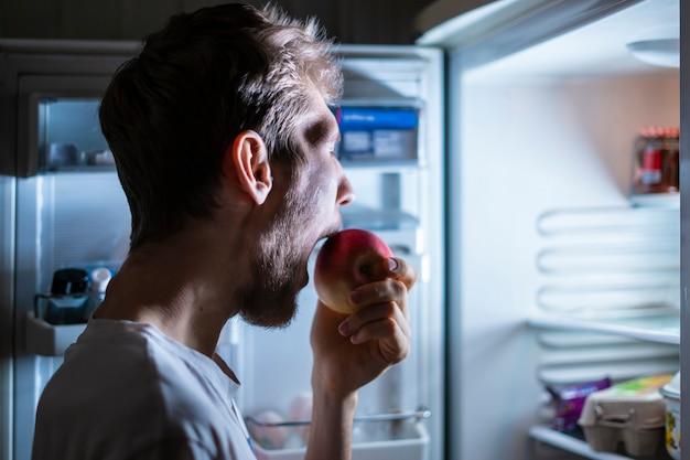 人は夜遅くに冷蔵庫から健康的な果物を食べるf