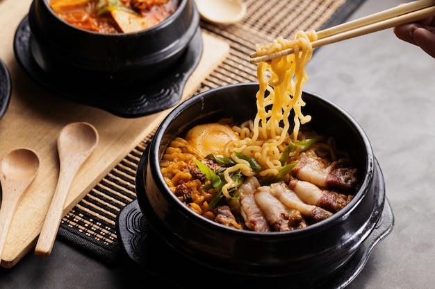 젓가락으로 검은 접시에서 중국 음식을 먹는 사람