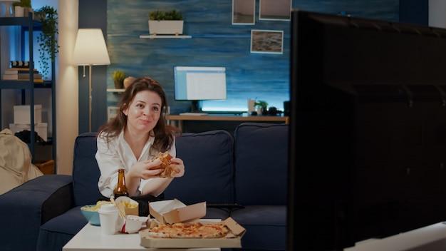 Человек ест вкусный гамбургер и картофель в гостиной