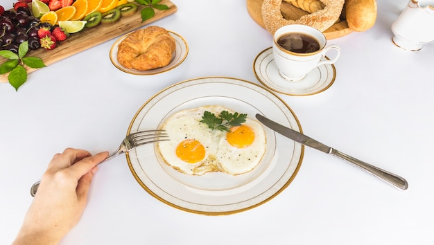 A person eating fried egg omelette with fork