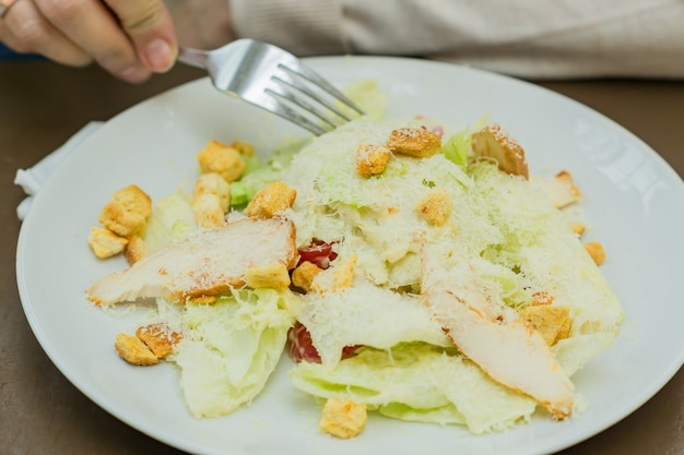 Person eating grilled chicken caesar salad with cheese, peking cabbage and croutons in the cafe