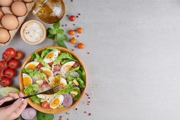 Человек ест здоровый салат из свежих овощей и вареных яиц